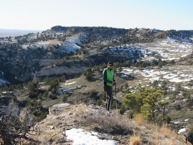 Jobe at the W end of the Wildcat Mountain summit area. Hogback Mountain, the most prominent peak in Nebraska, and single main objective of Jobe's trip, is seen behind him now just a mile off to the NW. (Prominence is a measure of the minimum elevation one would have to lose crossing land or water to reach a higher place.)