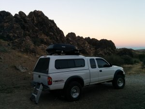 My white Toyota Tacoma sitting next to a rock escarpment at sunrise