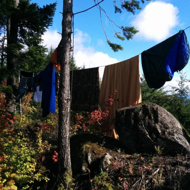 Bedding strung up on a rope between trees to dry out