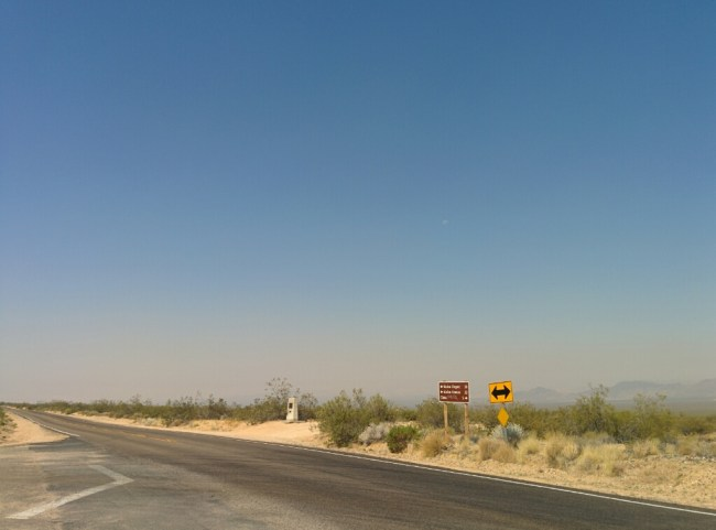 looking across Kelso-Cima Road to The Mojave Road Marker On A Hazy Day
