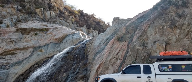Willow and the Tacoma in front of a waterfall in Baja