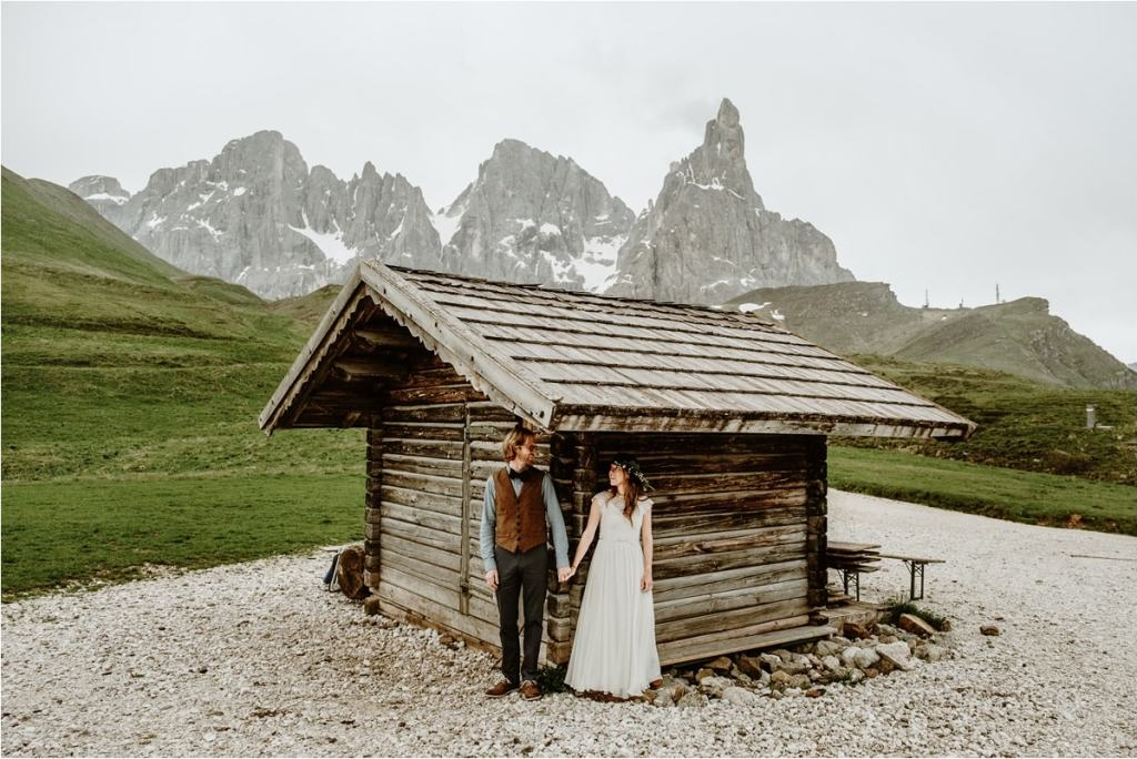The couple hides under the roof of a wooden hut in the Dolomites to escape the rain on their wedding day. By Wild Connections Photography