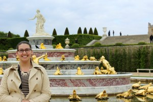 Travel Blogger Standing in Front of a Golden Fountain at the Gardens of Versailles, France