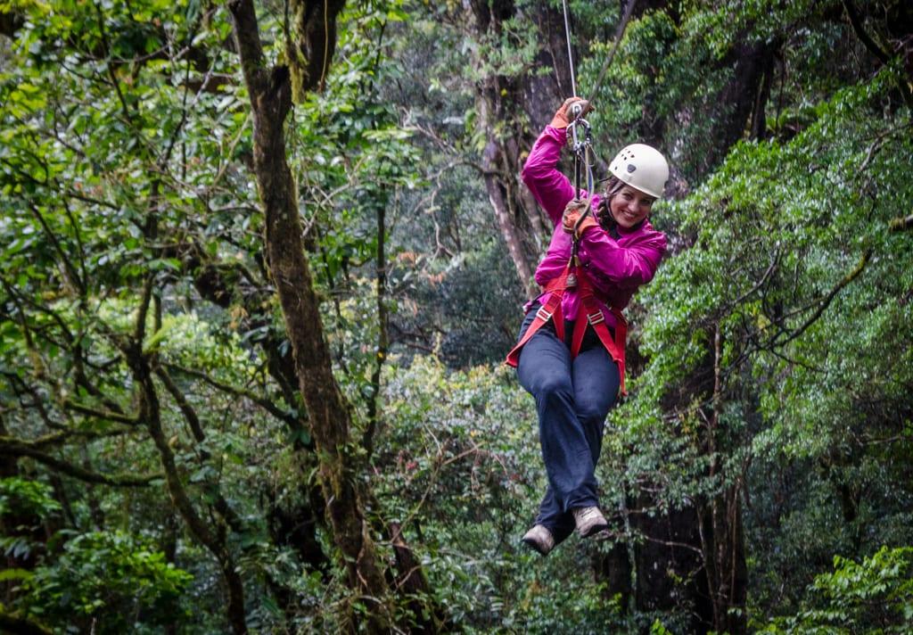 Kate Ziplining in a bright pink sweatshirt and black pants in Monteverde, Costa Rica