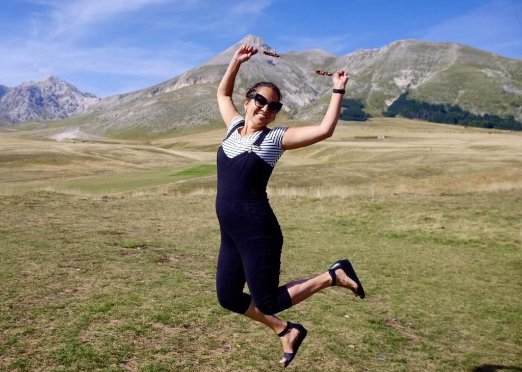 Kate wears overalls and jumps in the air in front of mountains.