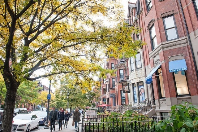 Brownstones and a sidewalk with trees with yellow leaves, Back Bay, Boston.