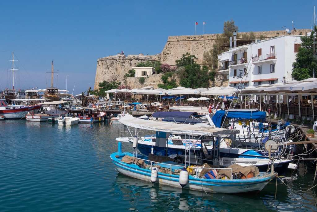 The waterfront of Girne, Cyprus: you see calm bright blue water, colorful wooden boats in the foreground and a tall stone fortress in the background, all underneath a bright blue sky.