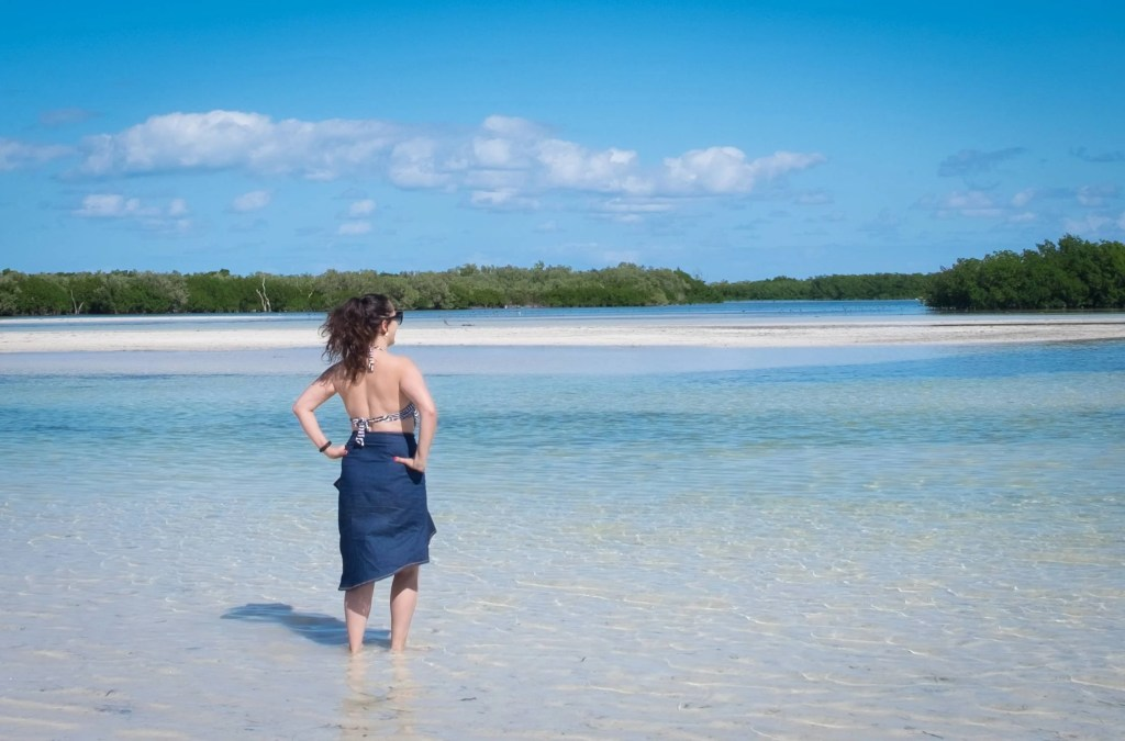 Kate wearing a long denim skirt and bathing suit top, facing outwards while standing in ankle-deep clear blue water in Holbox.
