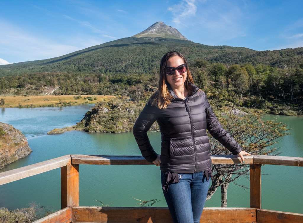 Kate stands in front of a bright green lake in Ushuaia with a mountain behind it.