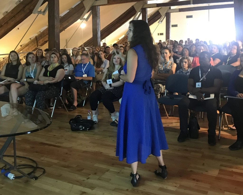 Kate is wearing a long bright blue dress and speaking toward a packed room with more than 60 people watch her giving a presentation.