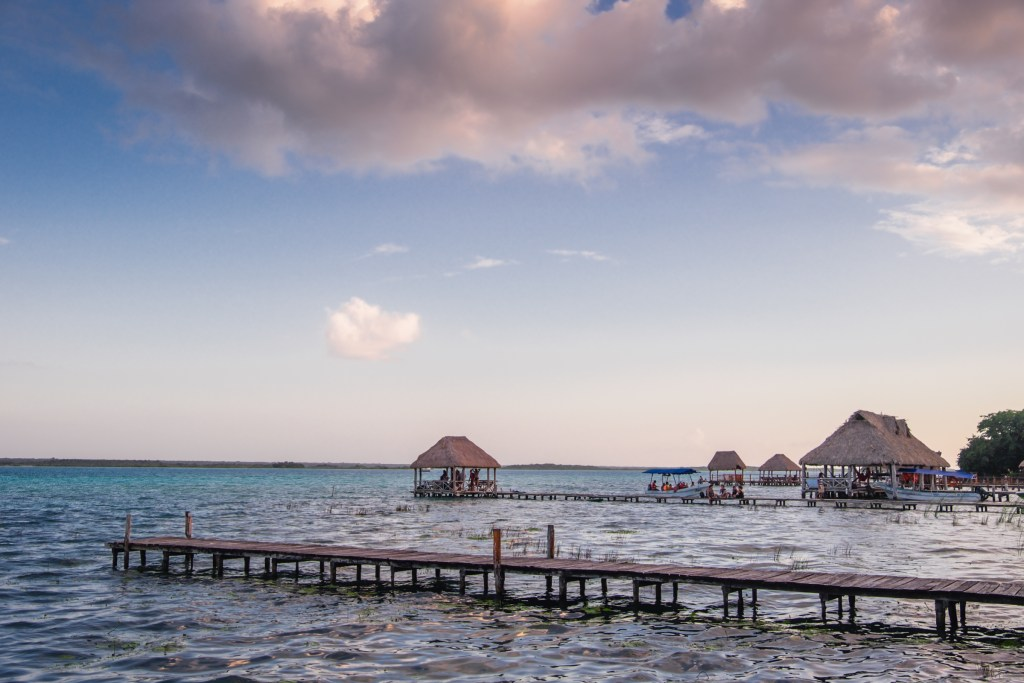 Huts on Bacalar Lagoon underneath a pink and blue sky.