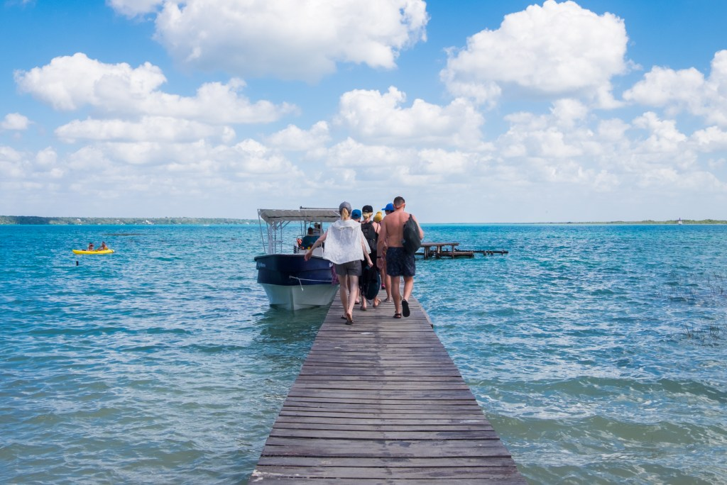 Friends walking down a dock in Bacalar, Mexico, blue lake on each side.