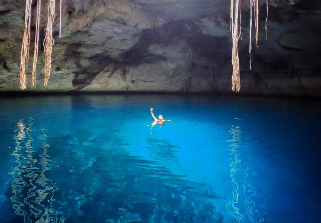 Kate swimming in the bright blue Cenote of Noh Mozon