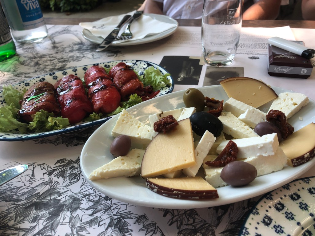 Plates of Serbian cheeses and stuffed red peppers.