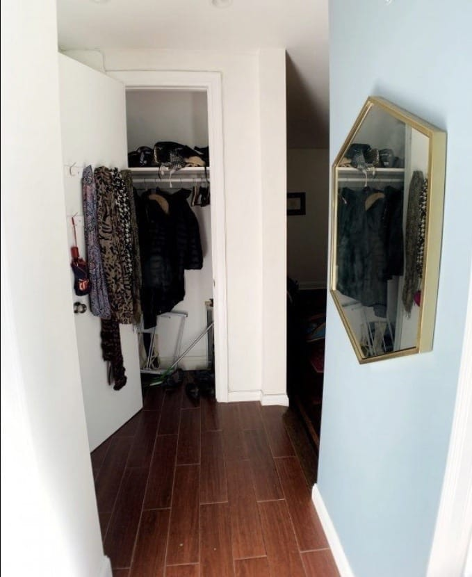 Kate's hallway leading to a closet with scarves hanging on the open door, and a gold hexagonal mirror on the right wall.