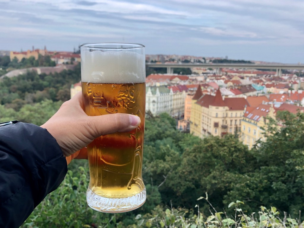 Kate's hand holds a beer while overlooking the treetops and yellow and orange buildings of Prague