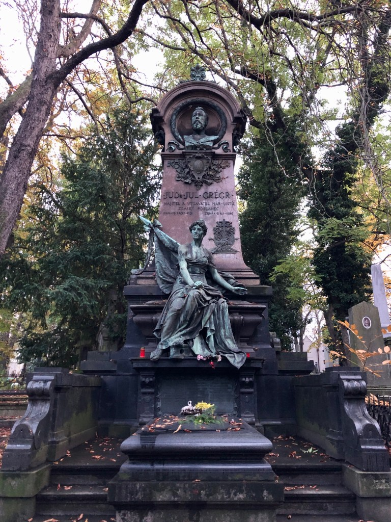 A giant gravestone featuring a man's head and a green angel statue.