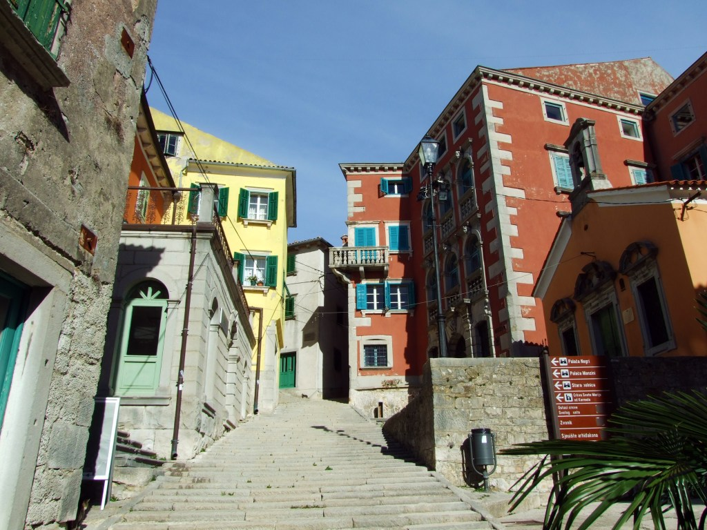 A stone staircase leading up into the pastel colored buildings of the town of Labin, Croatia.