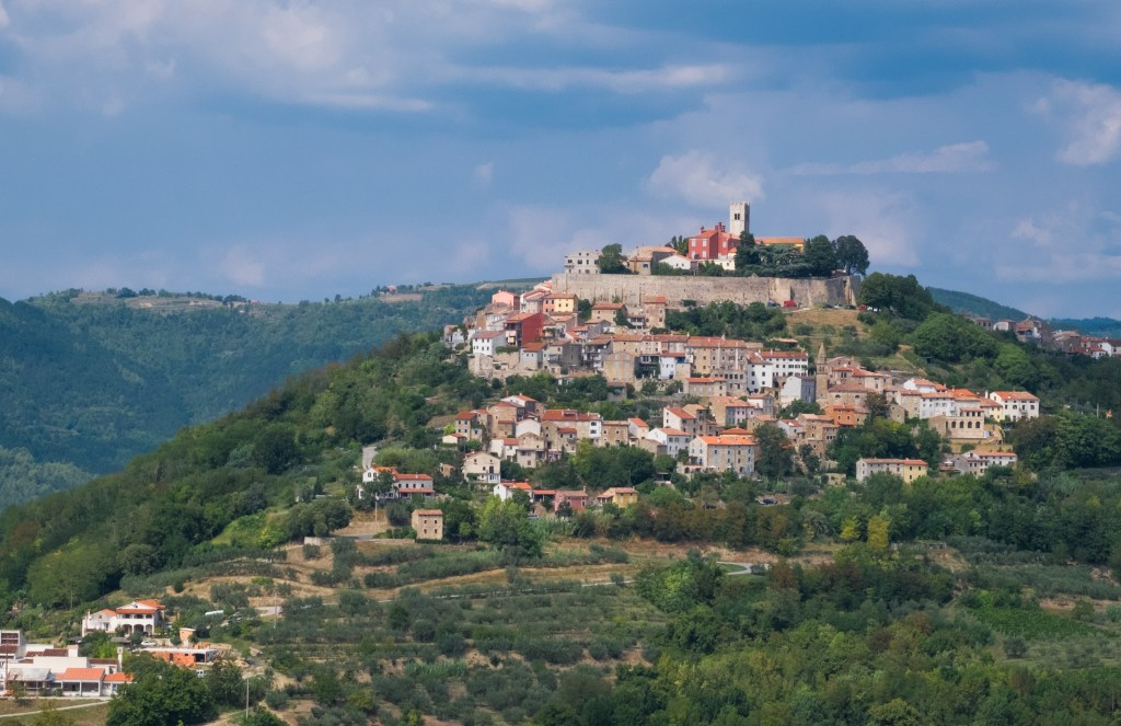 The town of Motovun: a small town build on top of a steep green hill, surrounded by a stone wall.