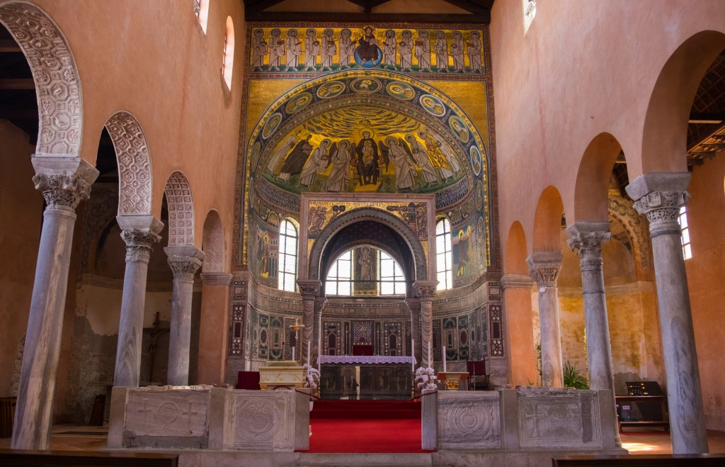 The Euphrasian Basilica of Porec, flanked with columns on each side and a gold Byzantine mosaic above the altar.