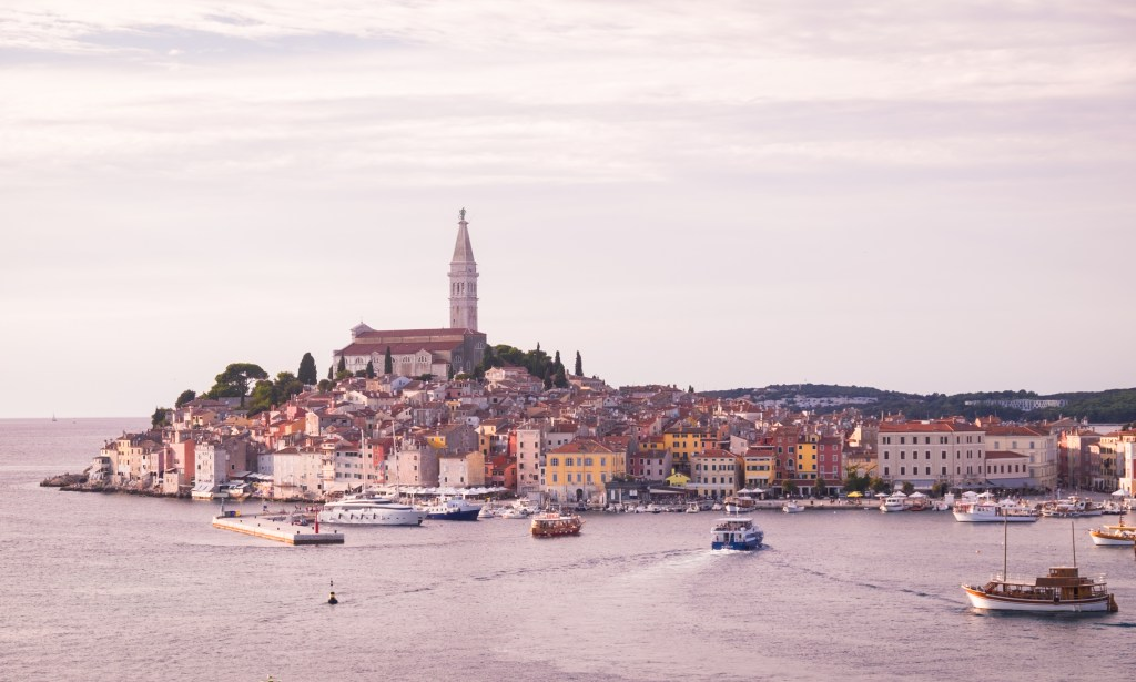 The town of Rovinj, lit up in pink just before sunset. You see the peninsula of the Old Town jutting into the sea, where a church tower pokes straight up from the center. Boats circle the water around the old town.