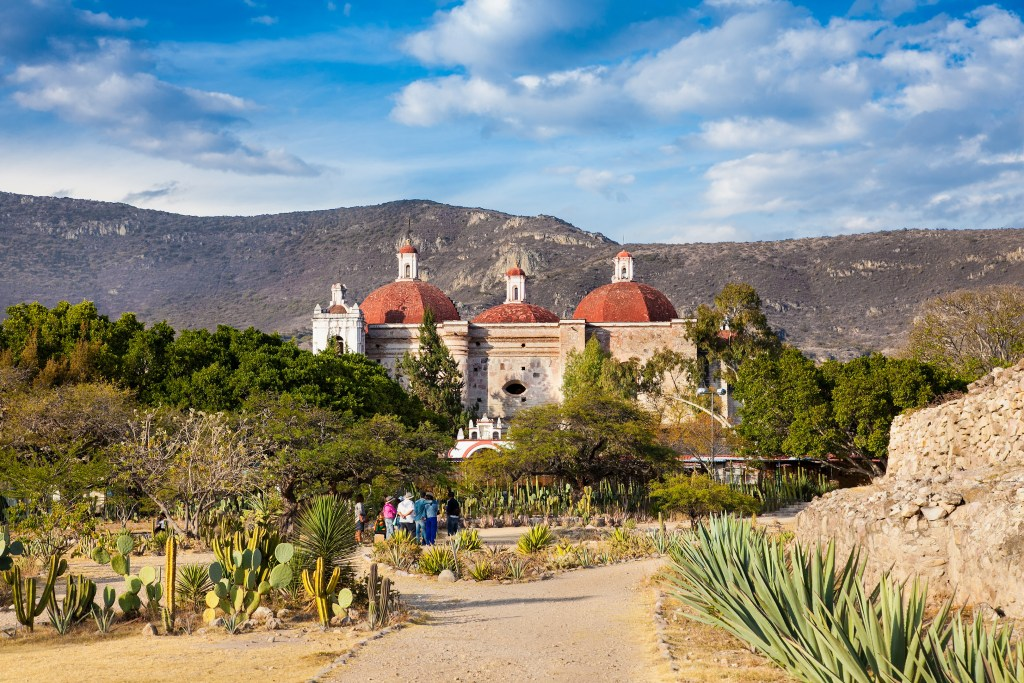 The town of Mitla with its beige stone building with three red domes. In front of it are cactus gardens and green trees; behind it are mountains.