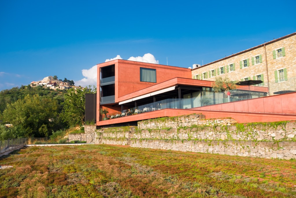 ROXANICH Wine Hotel, a modern pale red building with the Mountain View of Motovun in the background. In the foreground is a roof covered with green vegetation.