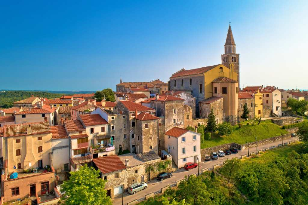 The town of Buje, Croatia, illuminated by sunshine. A small town with yellow buildings and terra cotta roofs, one church's steeple poking above the skyline, underneath a blue sky.
