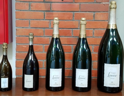 different sizes of champagne bottles on display at Maison Pommery. The smallest on the left is the regular size bottle you are probably used to seeing!