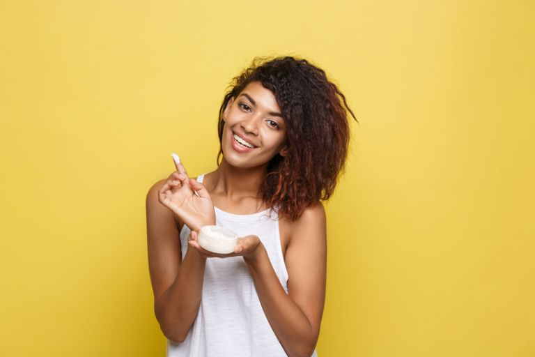 Beauty Concept - Beautiful young African American woman happy using skin care cream. Yellow studio background. Copy Space