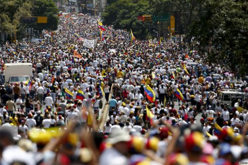 Street packed with Venezuelan protesters waving flags