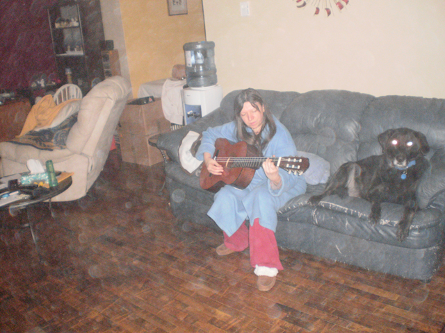 Cathi staying warm, playing guitar with Jassper.