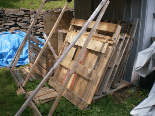 Pallets leaning against steel shed under a roof we can't see.