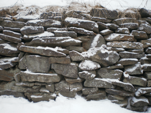 Dusting of snow on a stone wall.