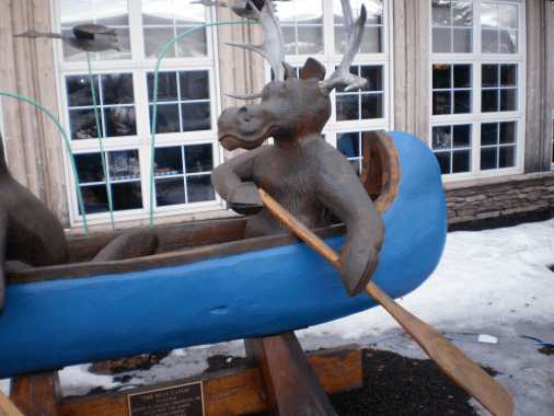 Sculpture of a Moose paddling a blue canoe.