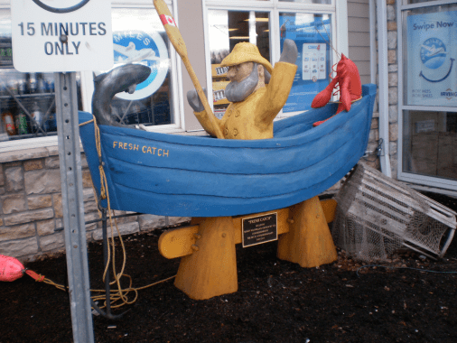 Sculpture of a Comical fisherman with a lobster and a jumping fish in a blue rowboat.