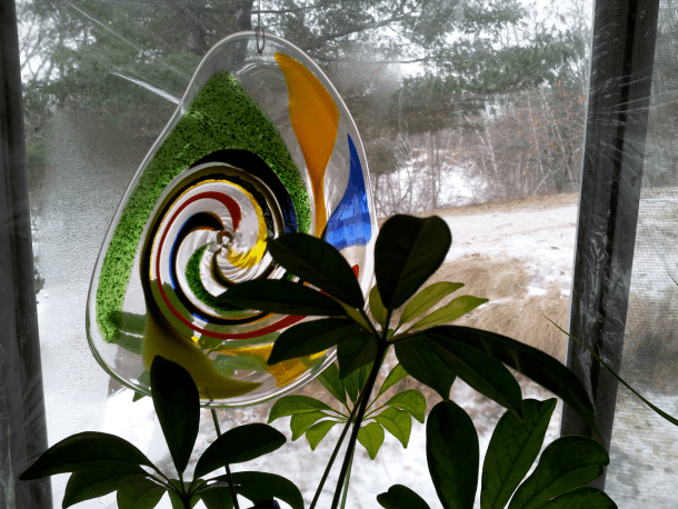 Decorative Glass with Colourful Swirl hanging in the porch window.