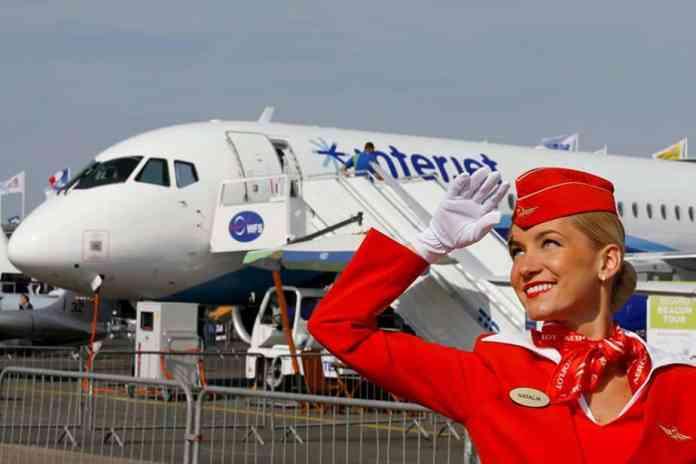 Aeromoça da Aeroflot em frente ao Superjet SJ100.