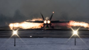 © Adam Duffield - A F/A-18C Hornet lights the burners to depart runway 25 at dusk - World Economic Forum Air Policing
