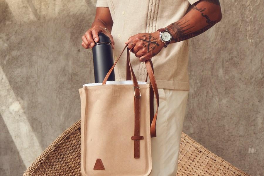 man holding camel Aerrem bag, putting in a black reusable water bottle