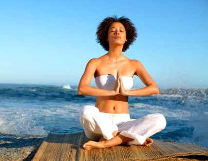 Meditating woman sitting cross-legged with back to the sea