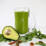 green smoothie in clear glass. Avocado laying beside drink.