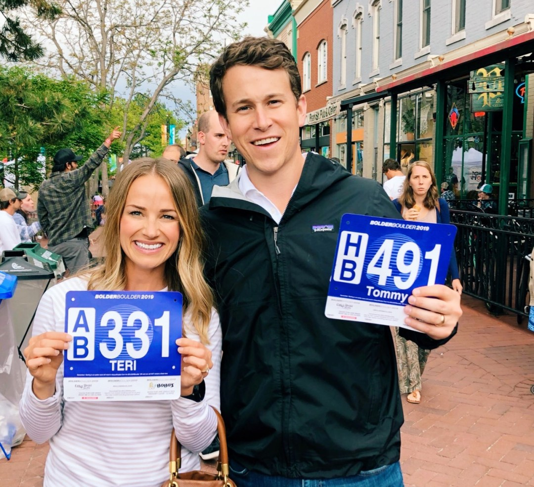 man and woman holding race bibs