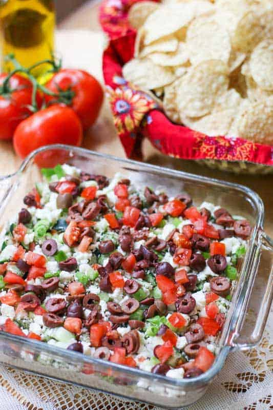 Need an appetizer that is tasty and can feed a crowd? This Greek Seven Layer Dip is a delicious spin off the traditional Seven Layer Dip with layers of hummus, tzatziki, feta, and veggie toppings.