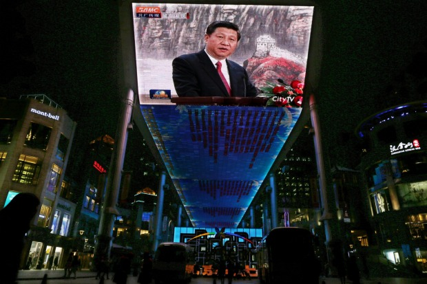 Rising power; A huge screen shows a broadcast of  Xi Jinping speaking in Beijing's Great Hall of the People.
