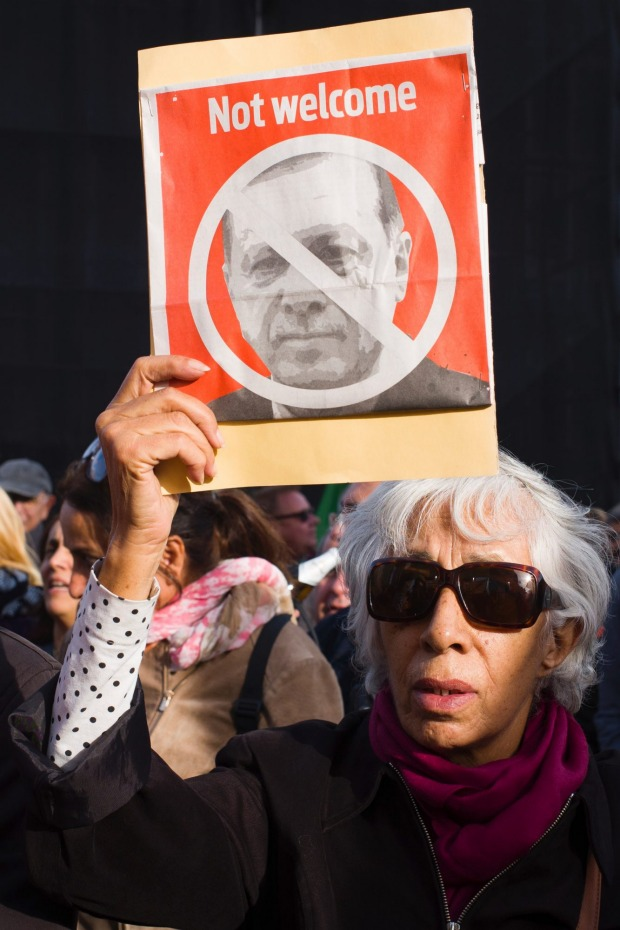A woman holds a poster to protest against the visit of Turkish President Recep Tayyip Erdogan to Berlin.