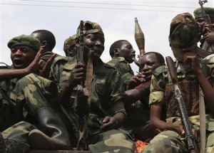 M-23 rebel fighters ride in a truck as they withdraw from Goma