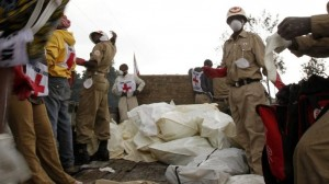 Red Cross workers collect bodies in body bags to load onto a truck in Ndosho near Goma