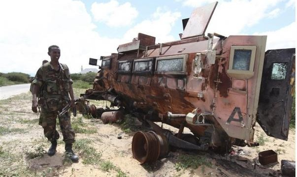 A Somali soldier looks at a burnt vehicle belonging to the AMISOM, as he patrols Dayniile district