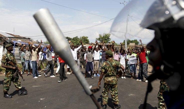 Proteste e agente con mitra